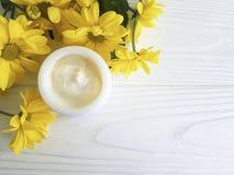 化妆润肤霜奶油香脂健康黄色菊花产品花白色木 免版税库存图片