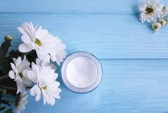化妆润肤霜面具框架精华产品在玻璃瓶子白花蓝色木背景中 库存照片