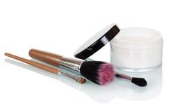 化妆用品刷子和奶油色银行白色背景的 库存照片