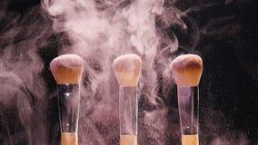 化妆用品刷子和爆炸五颜六色的构成粉末 股票录像