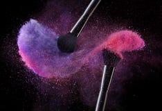 化妆用品刷子和爆炸五颜六色的粉末 库存图片