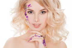 化妆用品和修指甲 可爱的妇女特写镜头画象有干燥花的在她的面孔,钉子设计的淡色 免版税库存照片