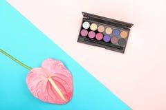 化妆用品和花在多色背景 免版税库存照片