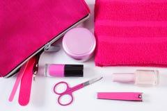 化妆用品和辅助部件修指甲或修脚的与桃红色袋子化妆用品,钉子关心的概念 免版税库存照片