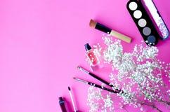 化妆用品布局在桃红色背景的与一棵装饰植物的分支 免版税库存照片