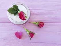 化妆用品玫瑰色瓶奶油有机生气勃勃关心自然手工制造在一种木背景商品组成 免版税库存照片