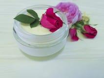 化妆用品玫瑰色瓶奶油治疗自然手工制造在一种木背景商品组成 免版税库存图片