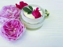 化妆用品玫瑰色瓶奶油生气勃勃关心自然手工制造在一种木背景商品组成 免版税库存照片