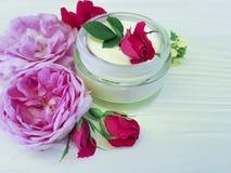 化妆用品玫瑰色瓶奶油生气勃勃护肤自然手工制造在一种木背景商品组成 免版税图库摄影
