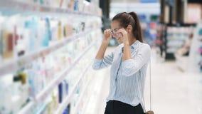化妆用品的女孩购物选择面霜,冲击由价格,慢动作 股票视频