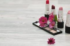 化妆用品的浪漫背景与花和化妆用品 套在白色的美丽的红色嘴唇 库存照片
