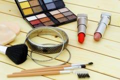 化妆用品被设置包括唇膏、眼影、海绵、刷子和镯子在木背景 图库摄影