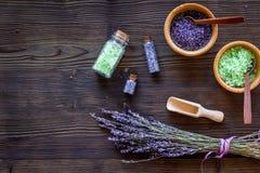 化妆用品集合用淡紫色草本和在瓶的海盐在木桌背景舱内甲板放置大模型 免版税库存照片