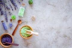 化妆用品集合用淡紫色草本和在瓶的海盐在石桌背景舱内甲板放置大模型 免版税库存图片