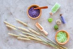 化妆用品集合用麦子草本和海盐在瓶在石桌背景舱内甲板位置 免版税库存图片