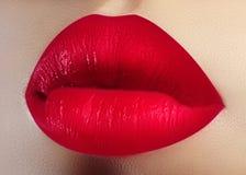化妆用品,构成 在嘴唇的明亮的唇膏 美丽的女性嘴特写镜头与红色嘴唇构成的 华伦泰甜亲吻 免版税库存图片