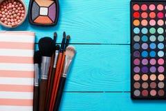 化妆袋子和在蓝色木背景组成产品 复制空间并且嘲笑  塑造夏天 顶视图 免版税库存照片