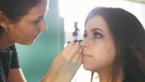 化妆过程在年轻黑发妇女的美容院-做眼睛的脸 股票录像