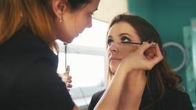 化妆过程在年轻黑发妇女的美容院-称呼的脸和的头发,接近  影视素材