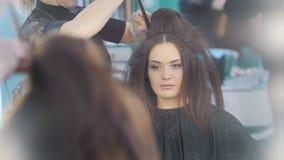 化妆过程在年轻黑发妇女的美容院-称呼的脸和的头发,接近  股票录像