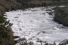 化学制品废物在河起泡沫 免版税库存照片