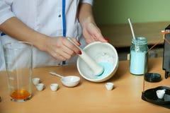 化学家由杵混合在灰浆的粉末 免版税图库摄影