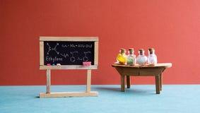 化学教训教室实验室 有分子式乙烯、木桌和化学制品的黑黑板 免版税库存照片