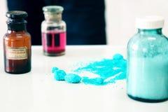 化学装瓶包含站立在实验室桌上的不同的颜色各种各样的物质被看见沿堆蓝色粉末 库存图片
