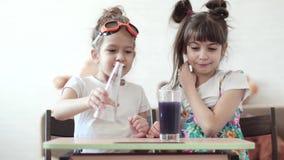 化工实验在家 孩子混合化学元素和由流动的反应惊奇