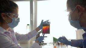 化工实验室、男人和妇女到玻璃和面具里做科学试验在大玻璃与液体 影视素材