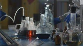 化工实验室 烧瓶的特写镜头有在桌上在慢动作站立,煮沸并且抽烟的化学制品的 股票视频