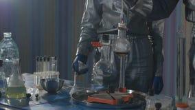 化工实验室 烧瓶的特写镜头有在桌上在慢动作站立,煮沸并且抽烟的化学制品的 影视素材