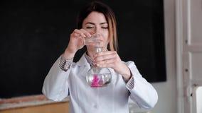 女性用不同的化学制品的科学家审查的烧瓶画象在医学实验室 影视素材