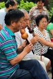 北京,中国- 2011年7月17日:妇女和人在传统长笛使用在景山公园 免版税库存照片