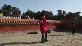 北京,中国2月2日2014年:老男人和妇女一起演奏空中陀螺在寺庙市场在汉语新春佳节期间在北京, 影视素材
