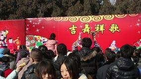 北京,中国2月2日2014年:访客为观看的小丑展示静立在寺庙市场在汉语新春佳节期间在北京, 股票视频