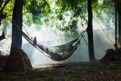 北宁市,越南- 2016年5月29日:休假的一个人在吊床的中午在树树荫下由Cau河 图库摄影