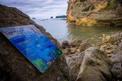 北岛,新的西兰16日2017年:与一个情报标志的美丽的多岩石的海滩,在大教堂小海湾海军陆战队员 库存照片