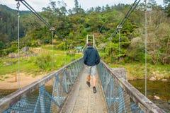 北岛,新的西兰16日2017年:走通过桥梁的未认出的人穿过河参观 免版税图库摄影