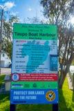 北岛,新的西兰18日2017年:陶波小船港口,小船舷梯的一个情报标志位于陶波,新 图库摄影