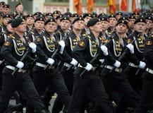 北方舰队的沿海力量的希尔克内斯红色横幅陆战队61旅团的海军陆战队员在游行期间的在红色平方 免版税库存照片