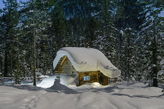 北方针叶林小屋与光亮线的冬天夜 免版税库存图片