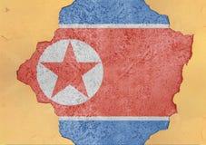 北朝鲜崩裂了孔和残破的旗子在大具体材料 免版税库存图片