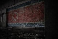 北朝鲜的被绘的旗子在肮脏的老墙壁上的在一个被放弃的被破坏的房子里 库存照片