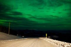 北极光在农村冬天路的夜空 免版税库存图片