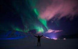 北极光在斯瓦尔巴特群岛,朗伊尔城市,卑尔根群岛,挪威墙纸山房子里  库存图片