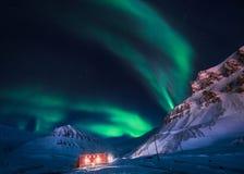 北极光在斯瓦尔巴特群岛,朗伊尔城市,卑尔根群岛,挪威墙纸山房子里  免版税库存照片