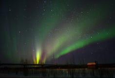 在一个领域的北极光与村庄 库存图片