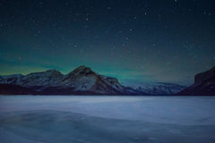 北极光-充分极光borealis和天空在山和湖minewanka,班夫国家公园,加拿大上的星 免版税库存照片