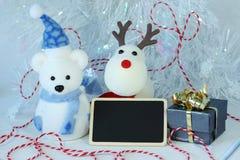 北极熊戴帽子的和圣诞晚会装饰的一条蓝色围巾与一则空的消息提名 免版税库存图片